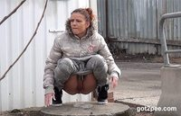 Sexy #brunette keeps a look out while she squats to #piss on an industrial estate